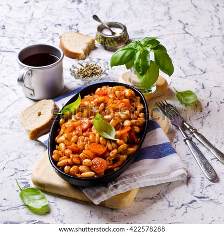 Baked beans in sauce with vegetables in rustic style. Selective focus. - stock photo