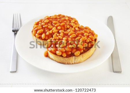 Baked beans on thick sliced white toast with knife and fork. An easy,nourishing meal.
