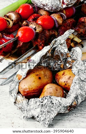 Baked beef and potatoes in foil on the coals - stock photo