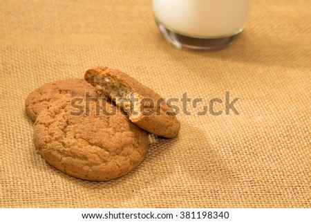 Baked biscuits and glass of milk on jute background - stock photo