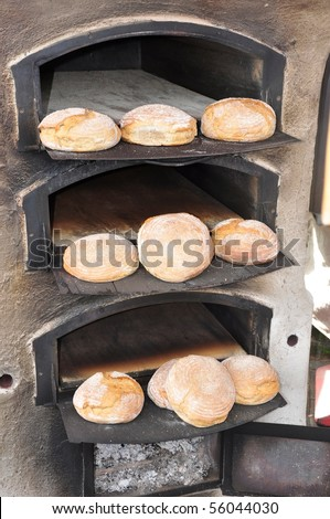Baked bread in old fashioned traditionel oven - stock photo