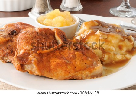 Baked breaded pork chops with mashed potatoes and applesauce