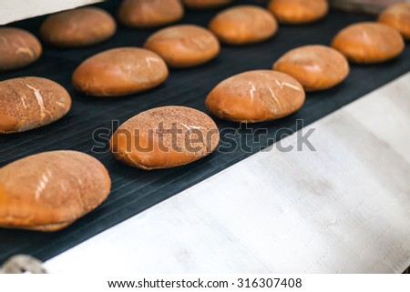 Baked Breads on the production line at the bakery - stock photo