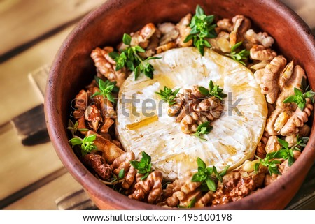 Baked brie cheese with honey, walnuts and thyme  (selective focus)