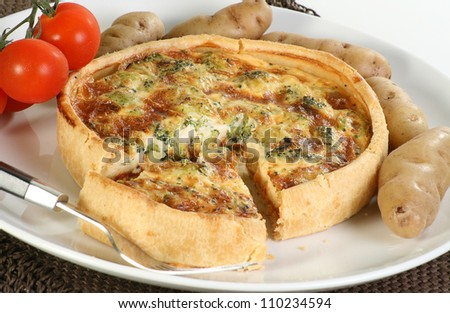 Baked brocoli and cheddar vegetarian quiche with tomatoes and new potatoes - stock photo
