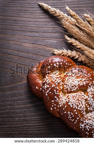 Baked bun wheat rye ears on wooden board food and drink concept.