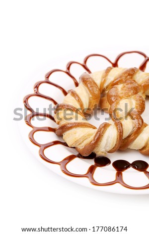 Baked bun with caramel pattern. Isolated on a white background. - stock photo