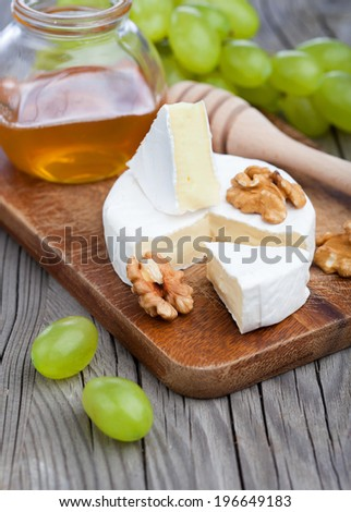 Baked Camembert cheese with honey, nuts and grapes on wooden background