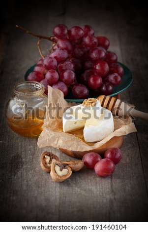 Baked Camembert cheese with honey, nuts and grapes on wooden background, selective focus