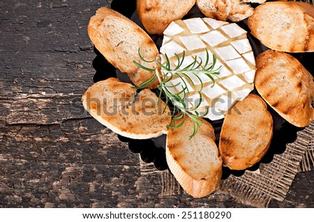 Baked Camembert cheese with rosemary and toast rubbed with garlic - stock photo