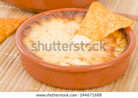 Baked Cheese - Melted cheese dip served with tortilla chips. - stock photo