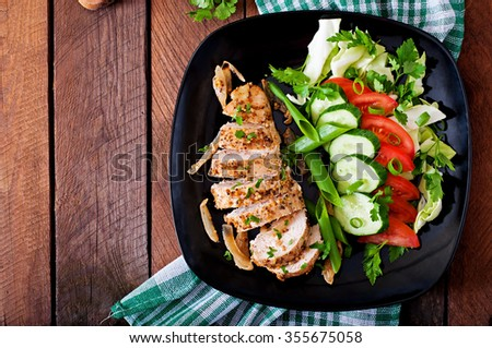 Baked chicken breast and fresh vegetables on the plate on a wooden background. Top view - stock photo