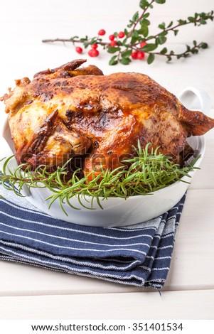 Baked chicken for Christmas dinner on white plate. - stock photo
