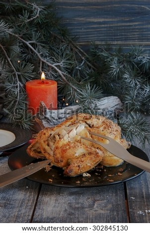 Baked chicken for Christmas on wodwn table - stock photo
