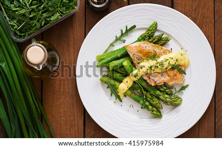 Baked chicken garnished with asparagus and herbs. Top view - stock photo