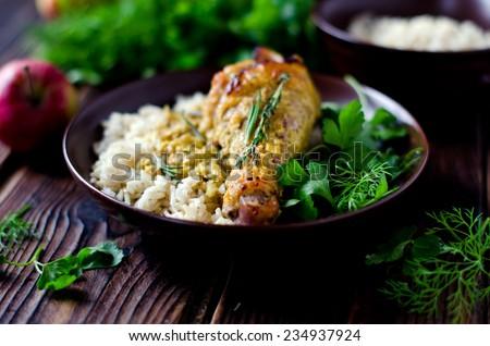 Baked chicken leg with rice garnish - stock photo