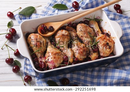 Baked chicken legs in cherry sauce and rosemary in dish for baking close up. horizontal