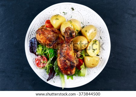 Baked chicken legs with potatoes and vegetables - stock photo
