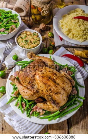Baked chicken stuffed with herbs and chilli peppers, couscous and delicious young beans with bacon - stock photo
