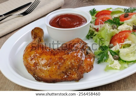 Baked chicken thigh with sauce and salad - stock photo