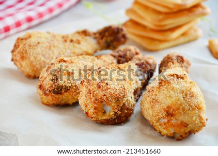 Baked chicken thighs in crispy cracker and cheese crust on white table - stock photo