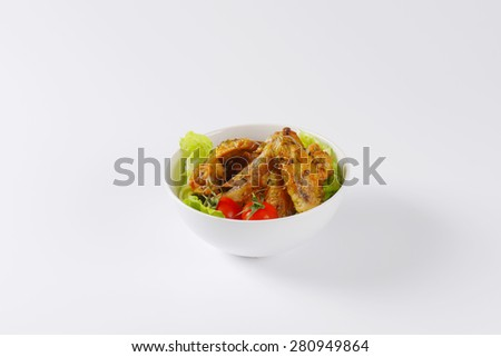 baked chicken wings, served with the salad in the bowl - stock photo