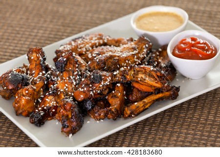 Baked chicken wings with barbecue sauce, sesame seeds, mustard and catchup