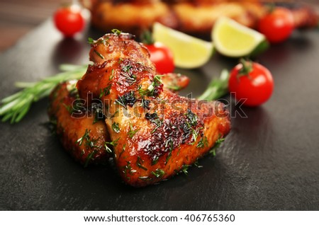 Baked chicken wings with tomatoes and rosemary on slate plate - stock photo