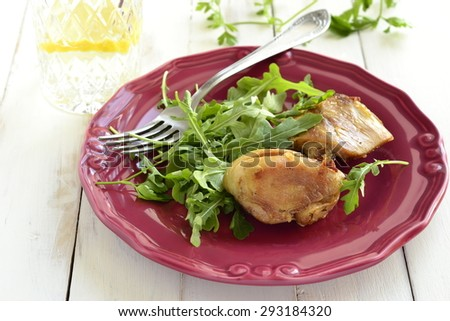 Baked chicken with arugula salad on a wooden background