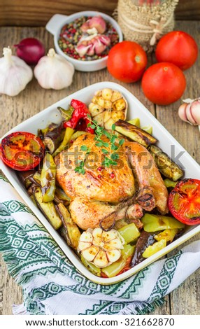 Baked chicken with eggplant, bell peppers, tomatoes, garlic and thyme. Dinner in a rustic style. Selective focus - stock photo