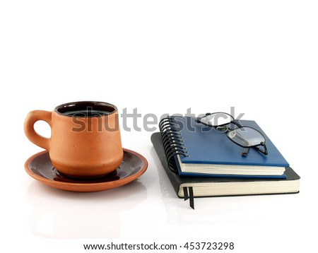 baked clay coffee cup with saucer and two diary books with eyeglasses isolated on white background - stock photo