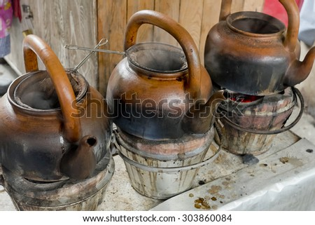 baked clay kettle with hot water on stove. - stock photo