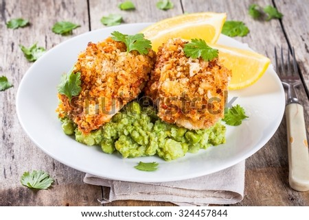 Baked codfish in breadcrumbs with mashed green peas and broccoli on wooden table - stock photo