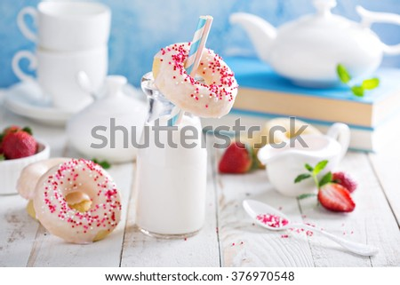 Baked donuts with pink glaze and sprinkles - stock photo