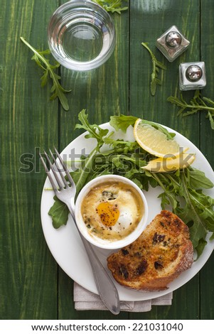 Baked egg with salad and bread on green wood table - stock photo