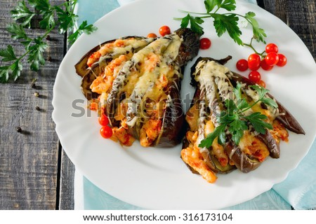 Baked eggplant with cheese, tomatoes and chicken on a dark wooden table
