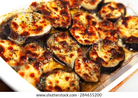 Baked eggplants with mozzarella and basil in a baking dish