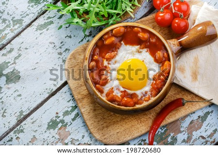 baked eggs with beans for Mexican  - stock photo