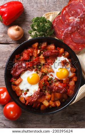 Baked eggs with chorizo and vegetables in the pan and the ingredients on the table. close up top view of the vertical.  - stock photo