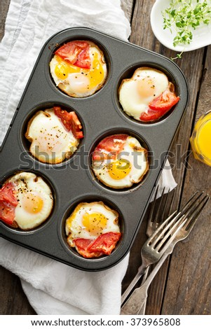 Baked eggs with ham and tomato in muffin tin - stock photo