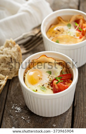 Baked eggs with ham and tomato in small ramekin - stock photo