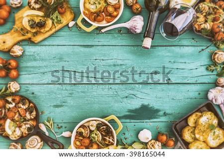Baked escargot in butter with herbs and tomatoes, frame with space for text - stock photo