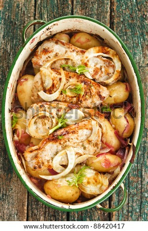 Baked fennel, pork, potatoes and red onions in an vintage enamel white cooking pot