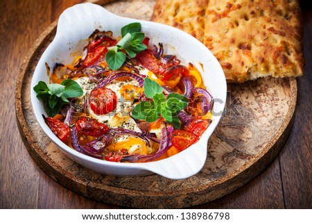 Baked feta cheese on vegetables and olive bread
