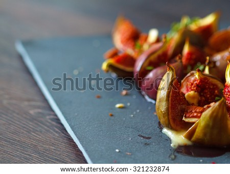 Baked figs with herbs, honey and nuts - stock photo