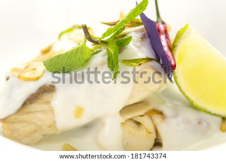 baked fish in cream sauce with lemon - stock photo