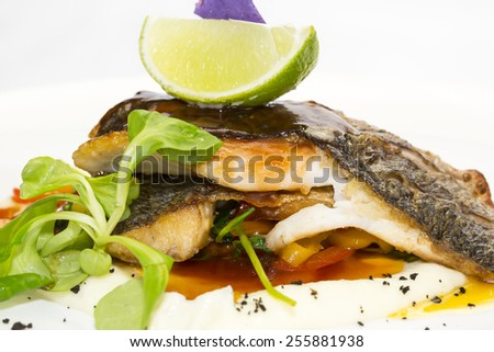 baked fish with vegetables and mushrooms in a restaurant - stock photo