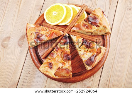 baked food : apple pies on wooden plate over table with cinnamon sticks and lemons - stock photo