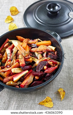 baked fruit and vegetables with almonds in the black cooking pan - stock photo