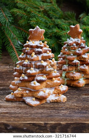 Baked gingerbread christmas tree with fresh evergreen branches on wooden table - stock photo